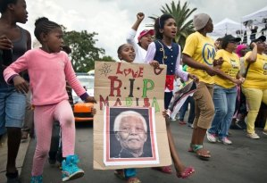 "A young girl with a placard showing the face of Nelson Mandela and referring to his clan name ""Madiba"", marches with others to celebrate his life, in the street outside his old house in Soweto, Johannesburg, South Africa, Friday, Dec. 6, 2013. Flags were lowered to half-staff and people in black townships, in upscale mostly white suburbs and in South Africa's vast rural grasslands commemorated Nelson Mandela with song, tears and prayers on Friday while pledging to adhere to the values of unity and democracy that he embodied (mail.com)"