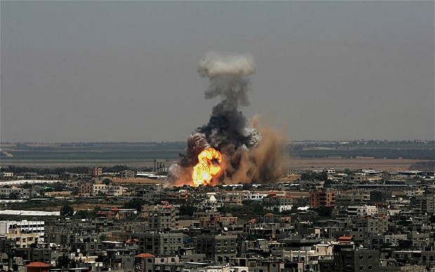 Photo credits: Corbis. Smoke and flames are seen following an alleged air strike which bombarded dozens of targets in the Gaza Strip, Israel on 8th July, 2014.