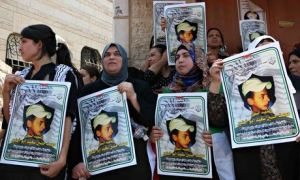 Photo credits: Anna Ferensowicz/Pacific/Barcroft. Women from Mohammed Abu Khdeir's family hold pictures of him outside his home in Jerusalem, Israel on the day of his funeral